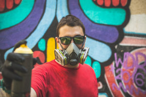 Graffiti artist holding spray color can