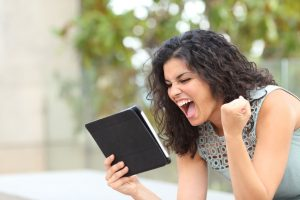 Excited girl holding a tablet and celebrating news