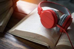 Concept of audiobook. Books on the table with headphones put on