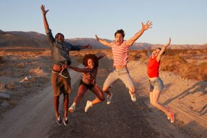 Young adult friends having fun jumping in the desert